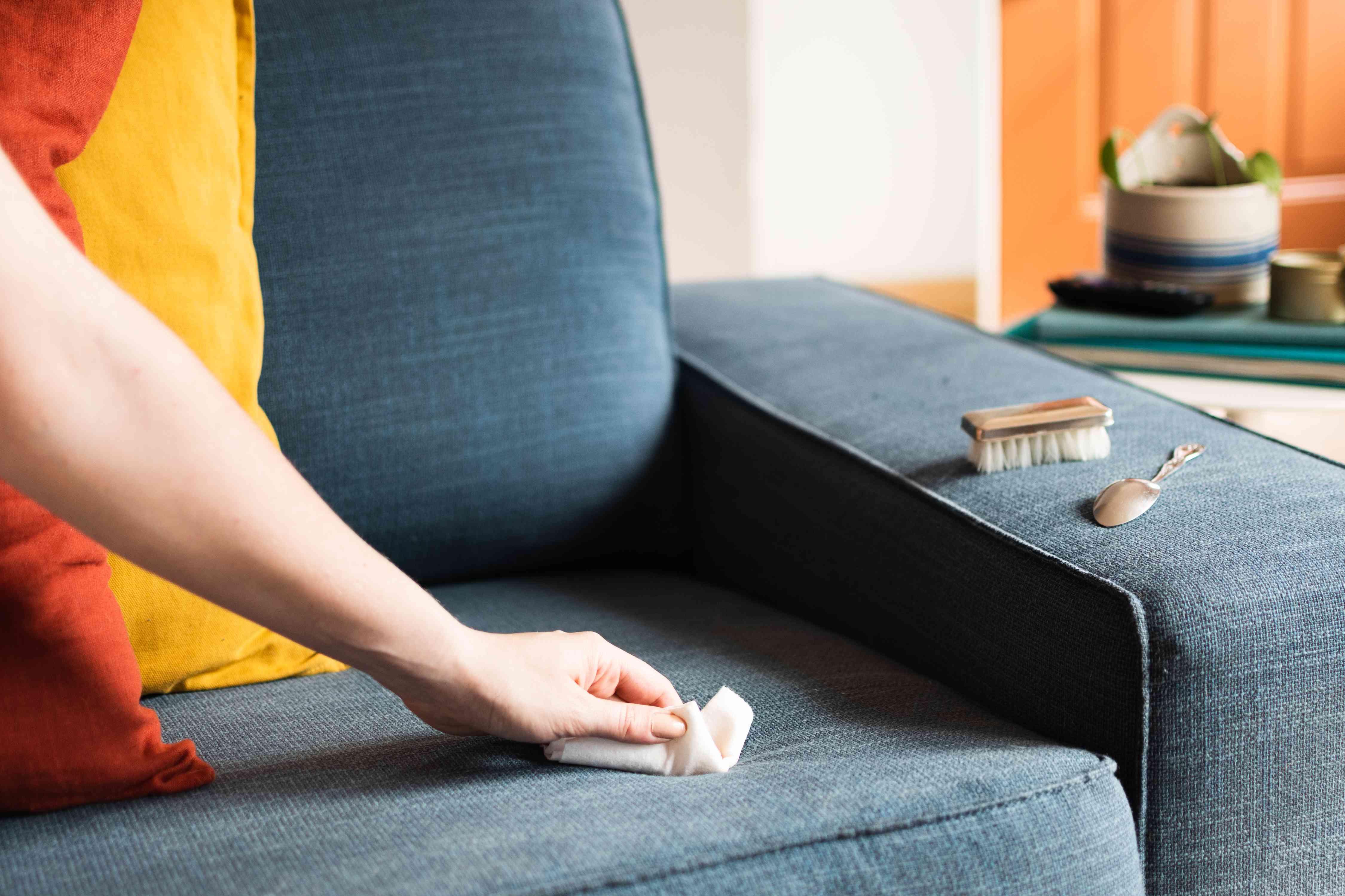 Khăn giấy thấm vết chất lỏng trên ghế dài bọc nệm màu xanh lam bằng bàn chải lông mềm và thìa trên phần kê tay