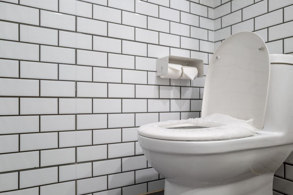 A toilet bowl decorated with white tiles.