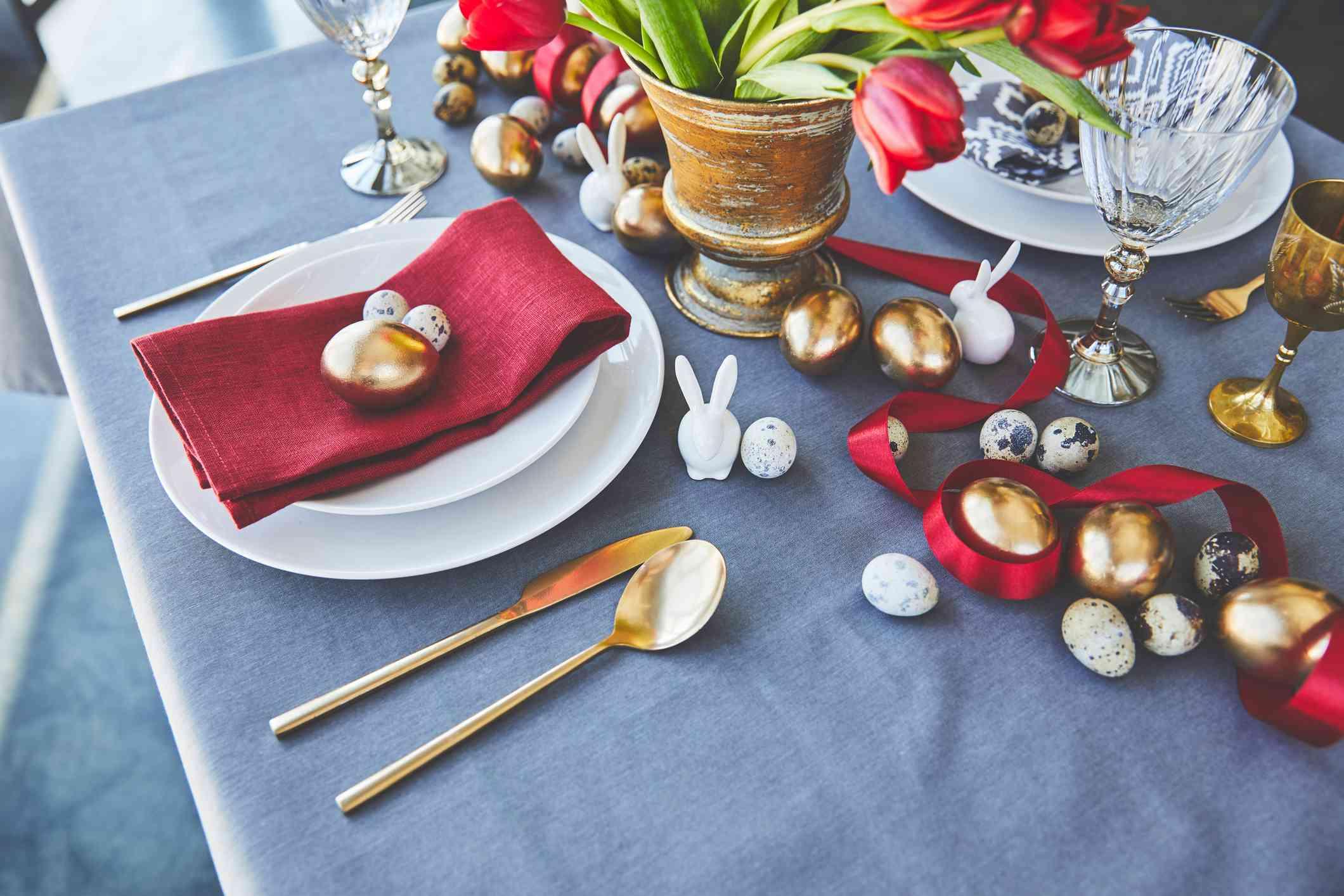 vista de ángulo alto de huevos de pascua dorados y flores en la mesa festiva del restaurante
