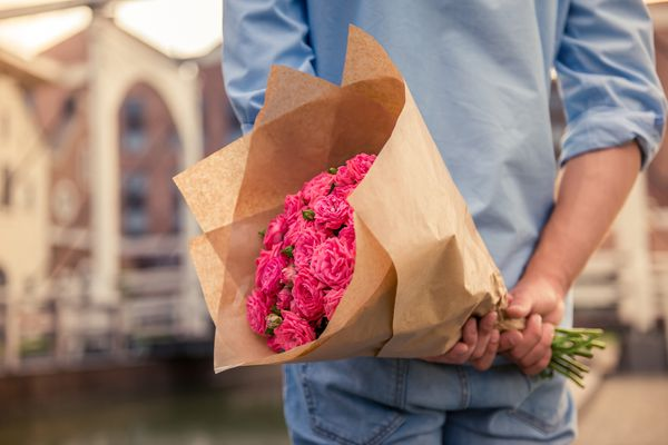 Young man holding pink flowers