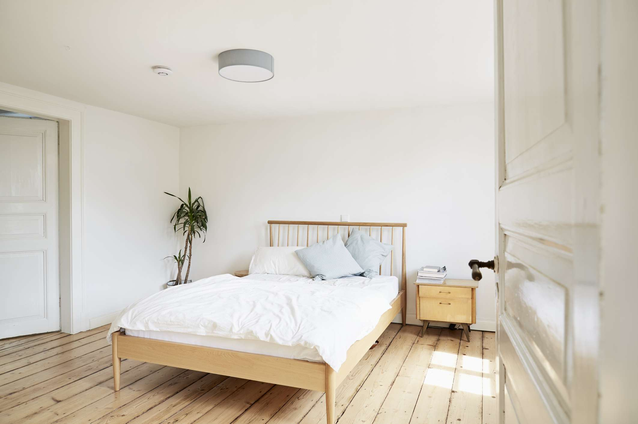 Bright modern bedroom in an old country house, with no storage under the bed