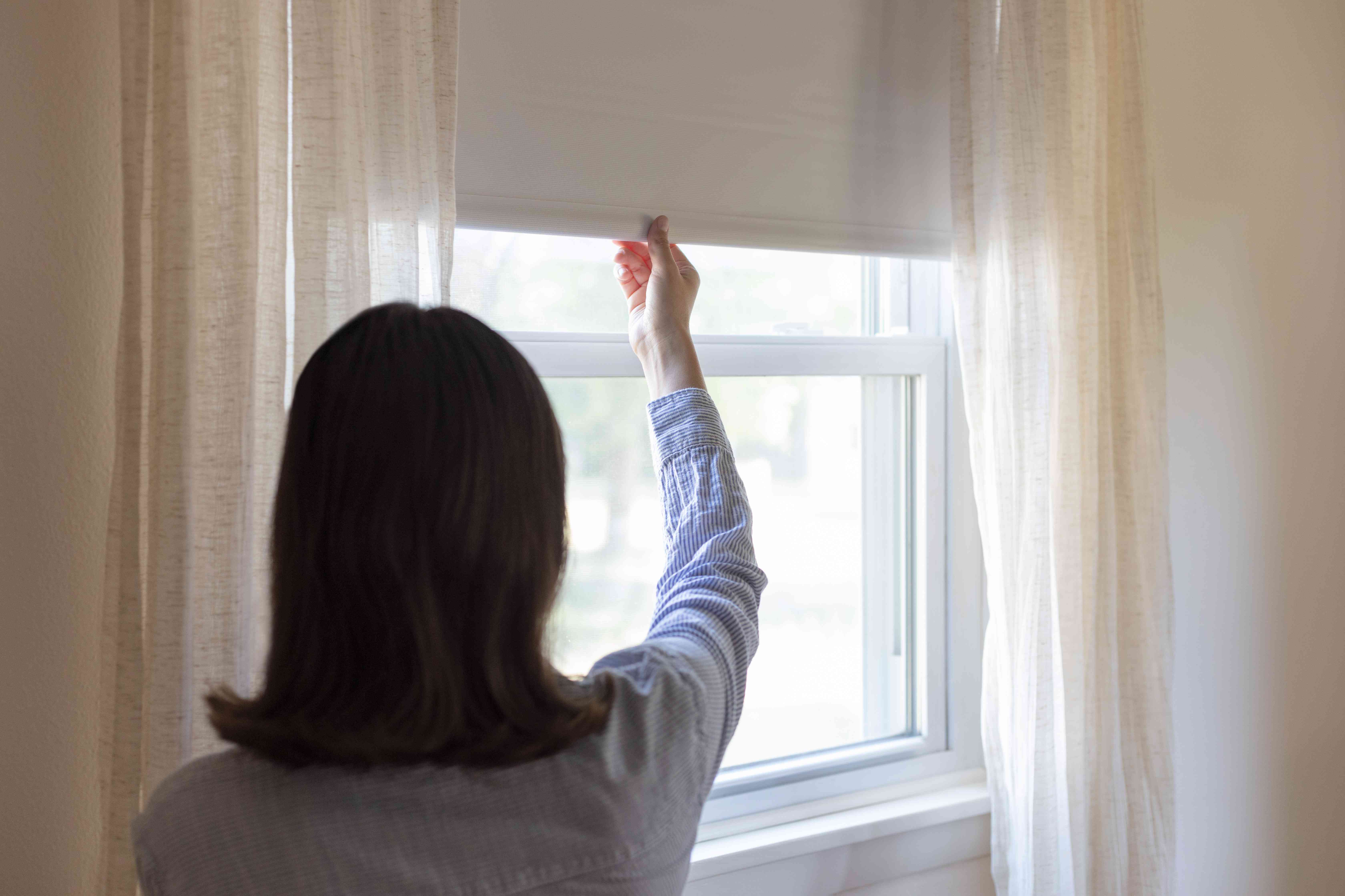 Window blinds being pulled down to lower electric bill