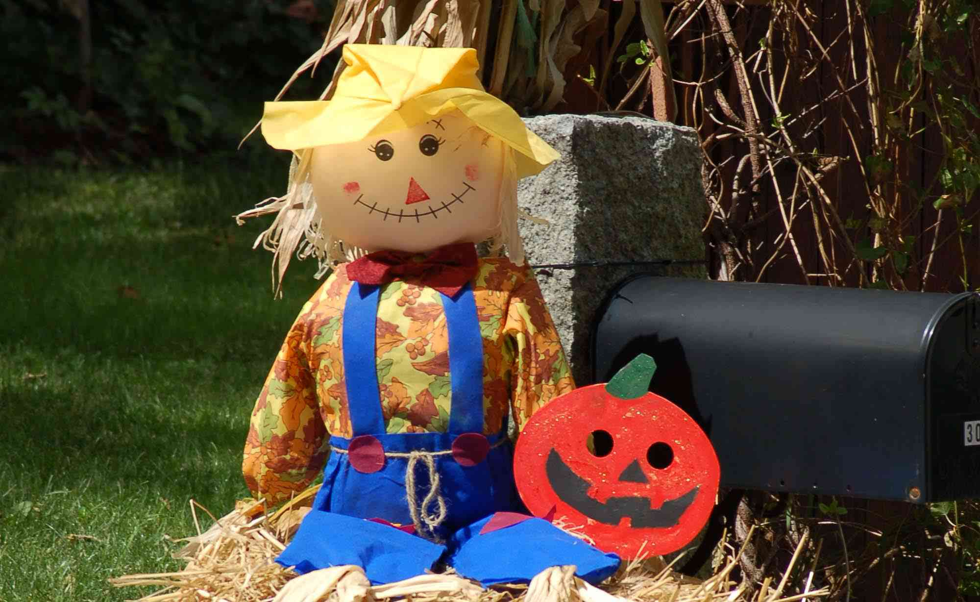 Scarecrow sitting on hay bale