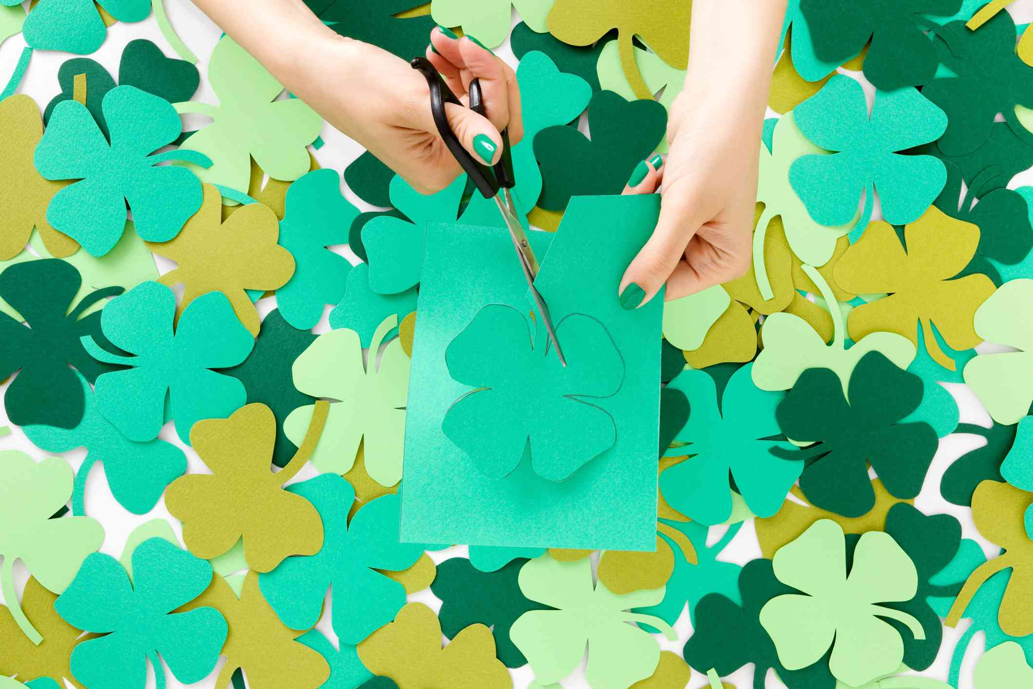 woman cutting out paper shamrocks