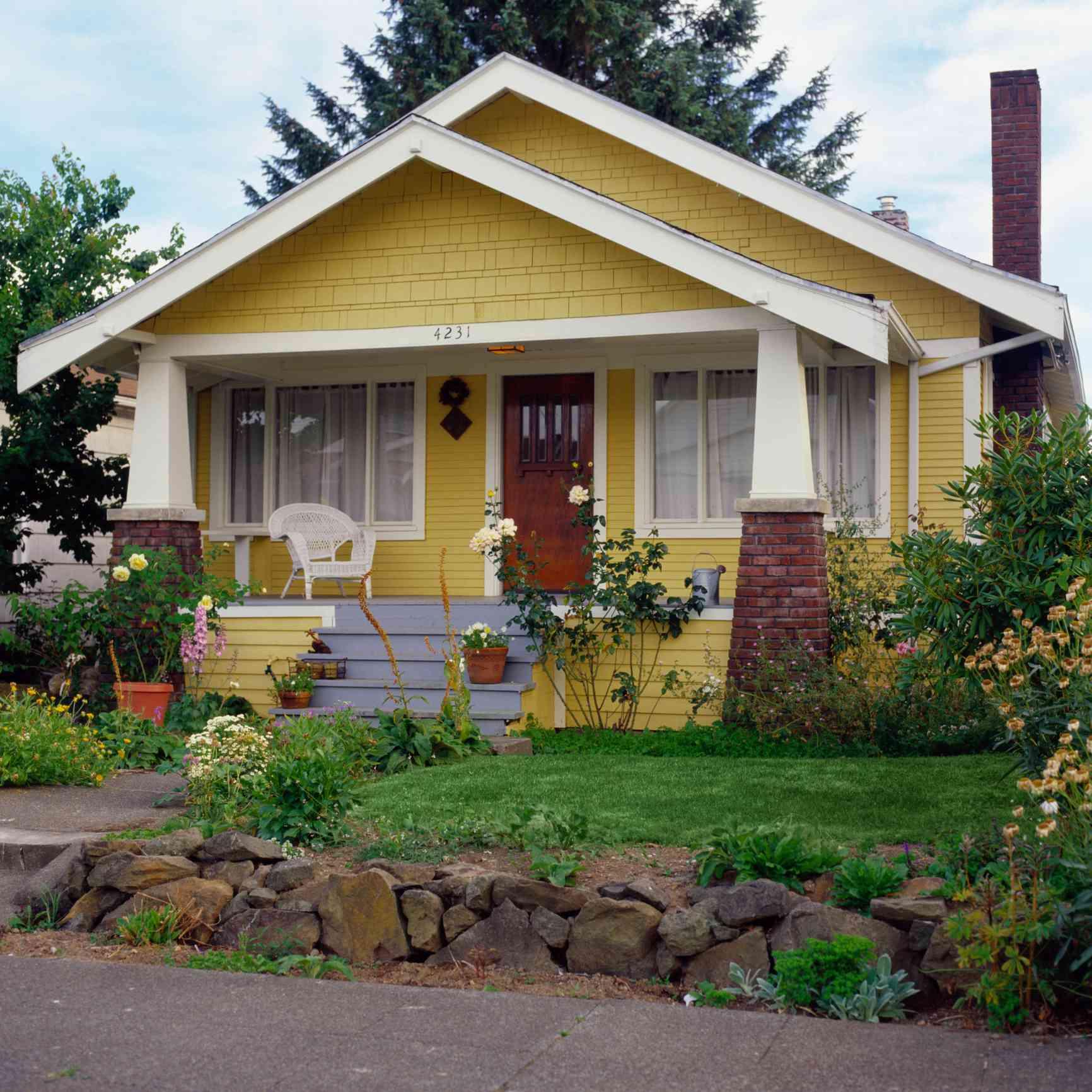 Casa de estilo bungalow amarillo con jardín, vista exterior