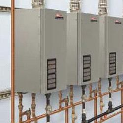 Multiple tankless gas hot water heaters mounted on a wall.