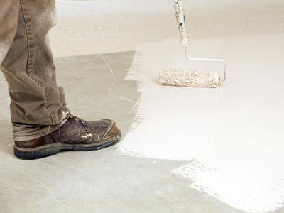 Painter Rolling Epoxy Paint on Concrete Floor