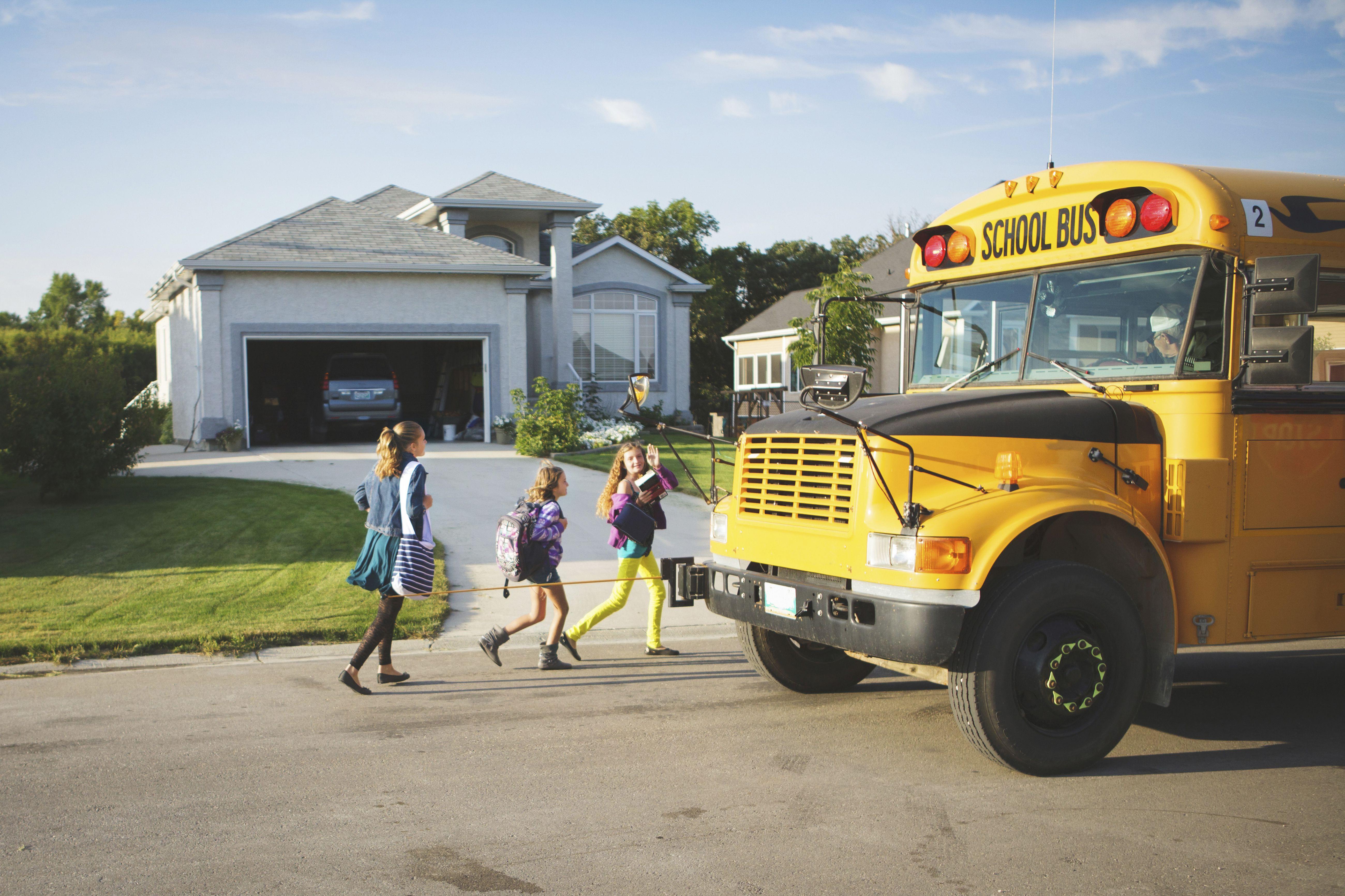 Niñas caucásicas caminando al autobús escolar