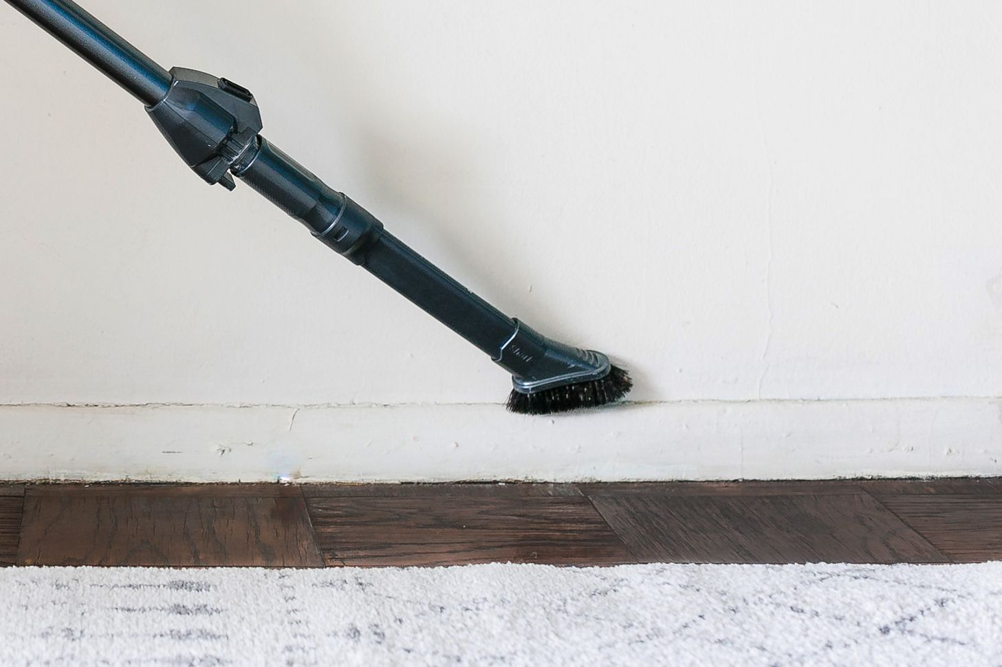 using the vacuum brush attachment on a baseboard