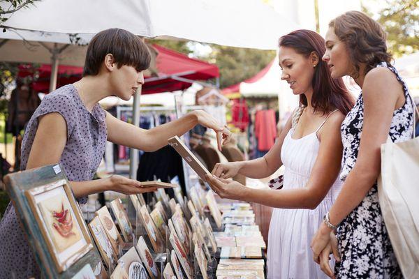 Shoppers browsing paintings at artisan flea market
