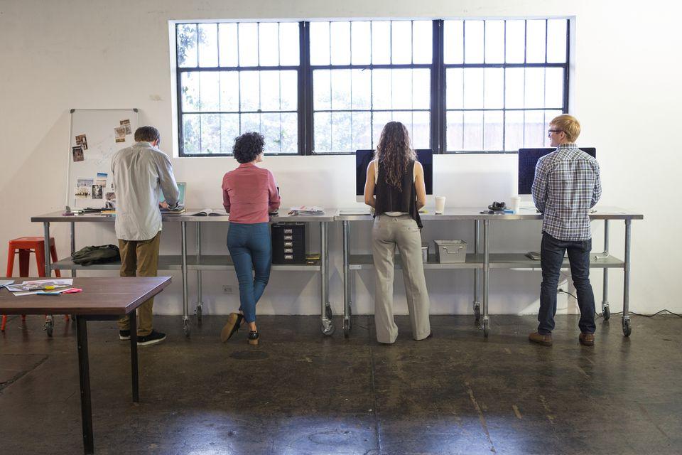 cuatro adultos en escritorios de pie