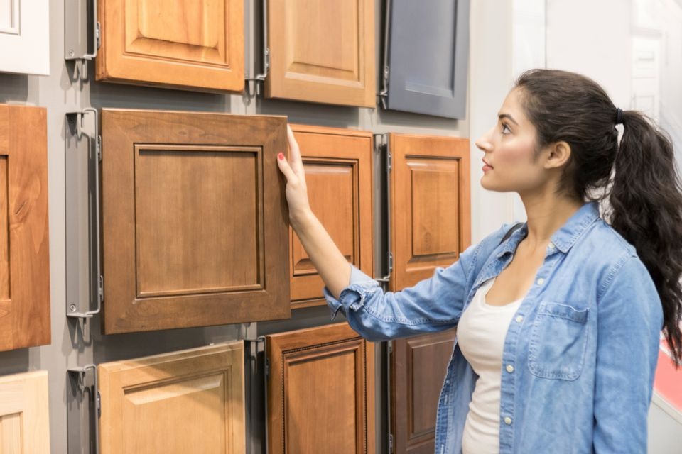 Female home improvement store customer examines wooden cabinets