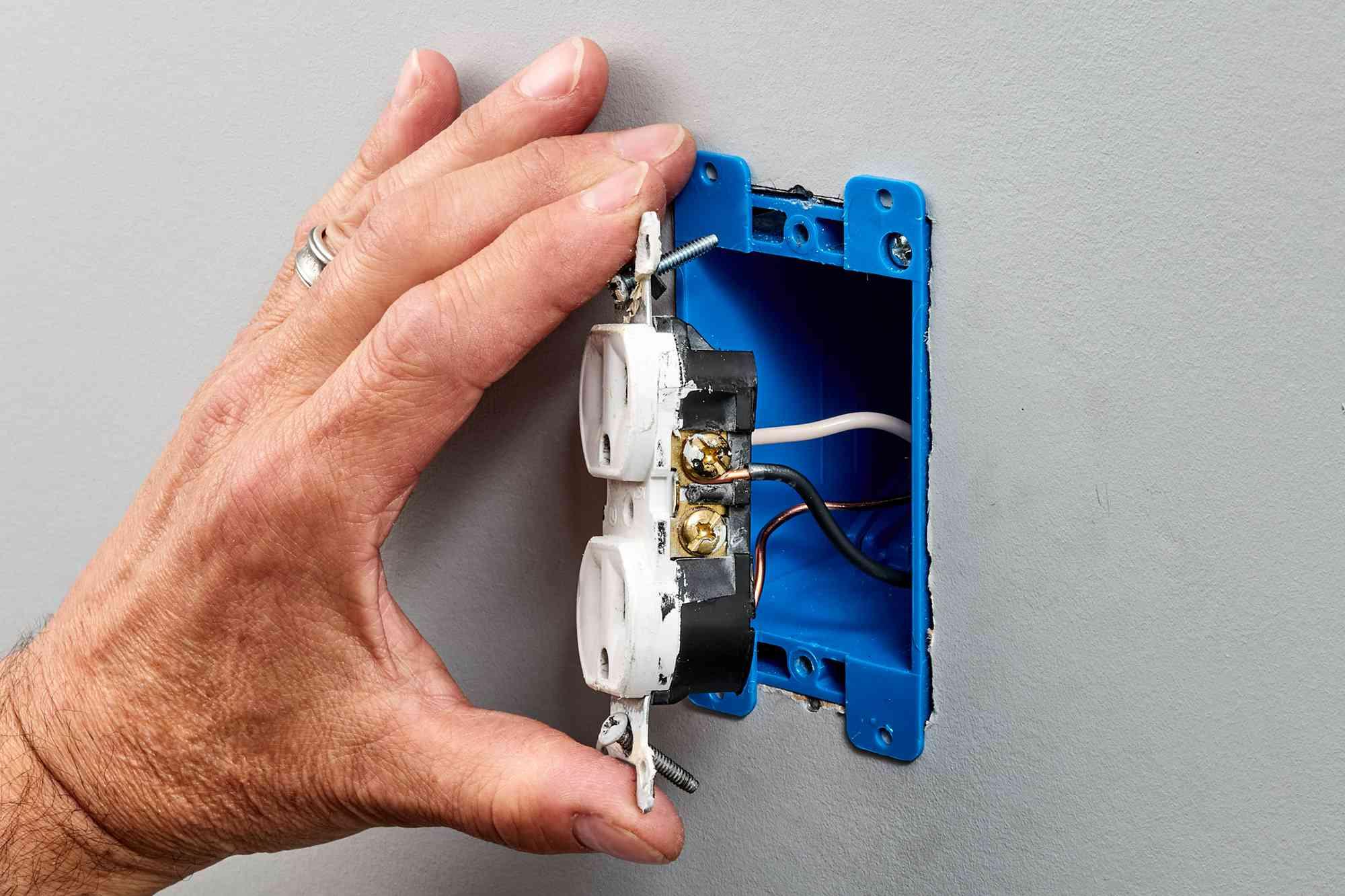 Receptacle held by metal strap to examine wiring