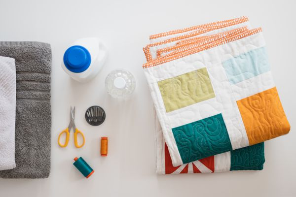Homemade quilt folded next to materials and tools for washing