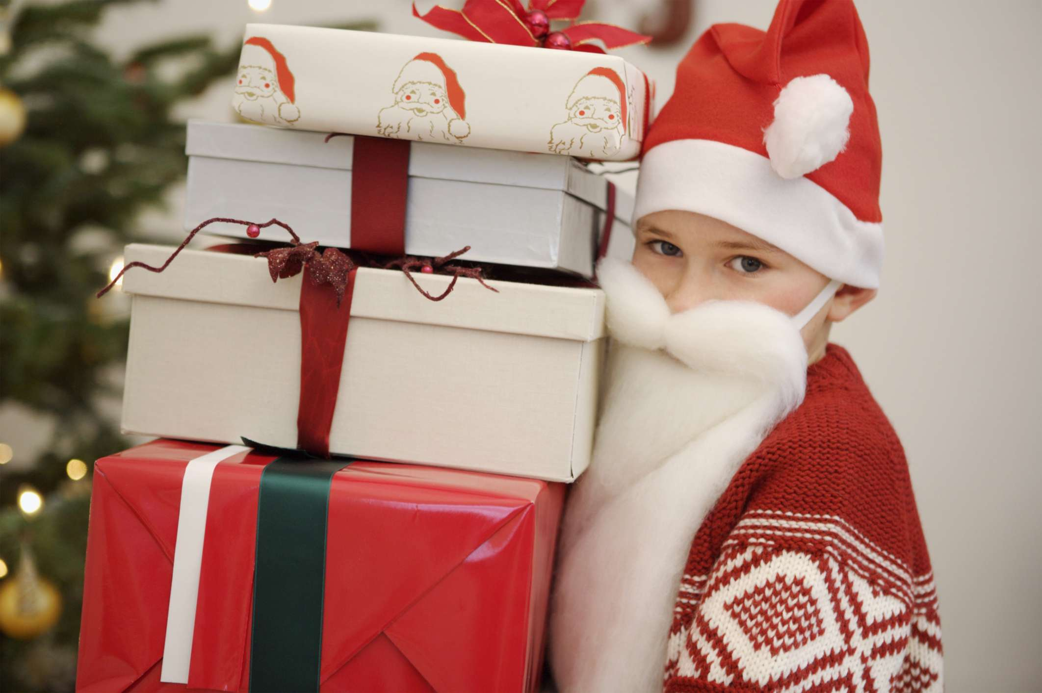 a boy dressed as santa holding a stack of gifts