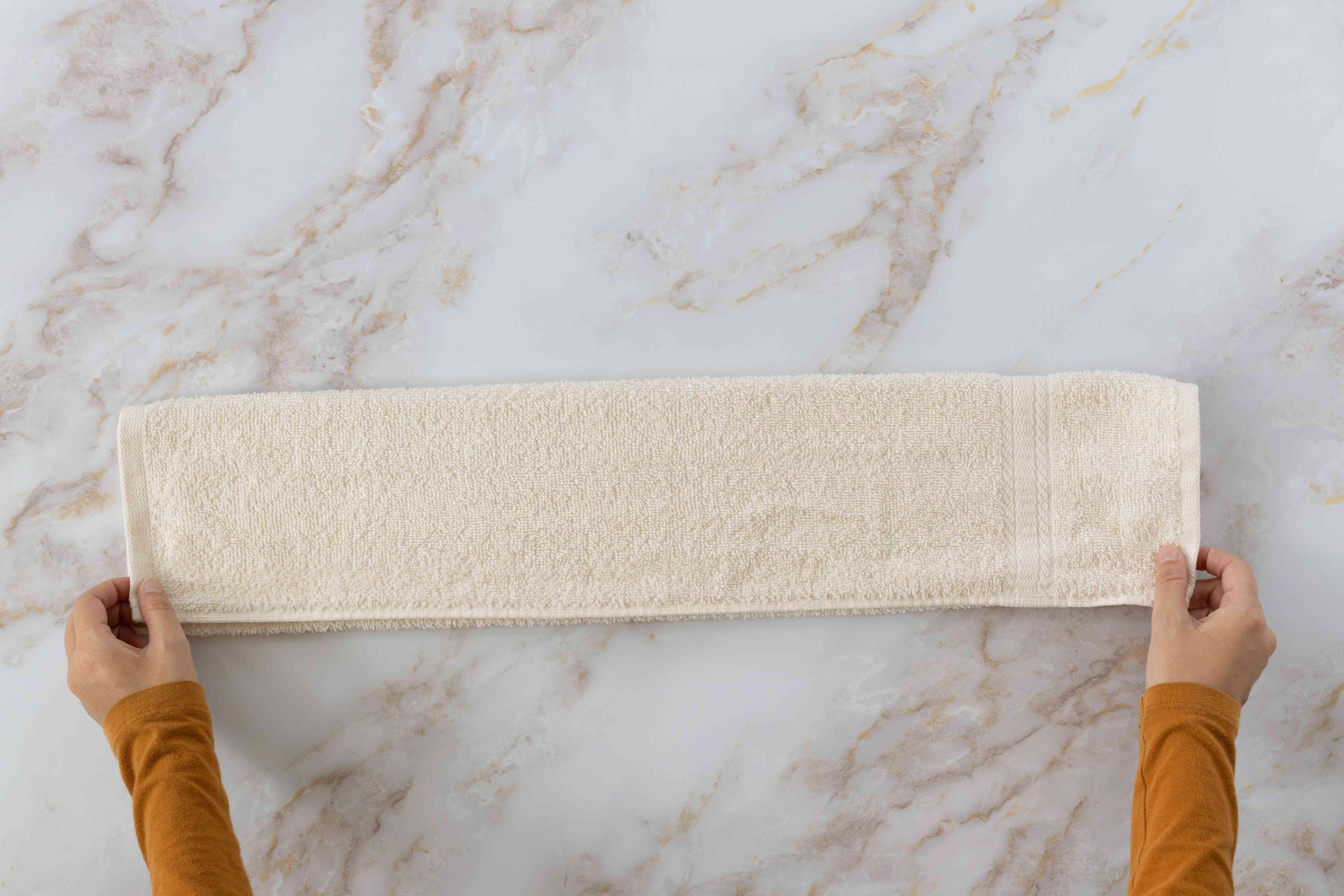 Cream towel folded as a three-layer strip long ways