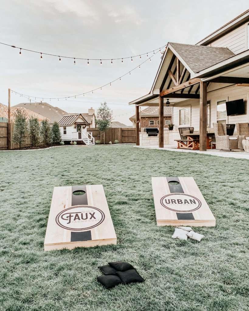 Two cornhole boards in a backyard