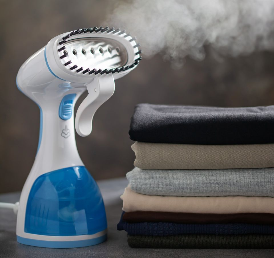 Portable clothes steamer with stack of folded clothes