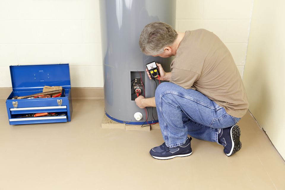 A plumber working on a water heater
