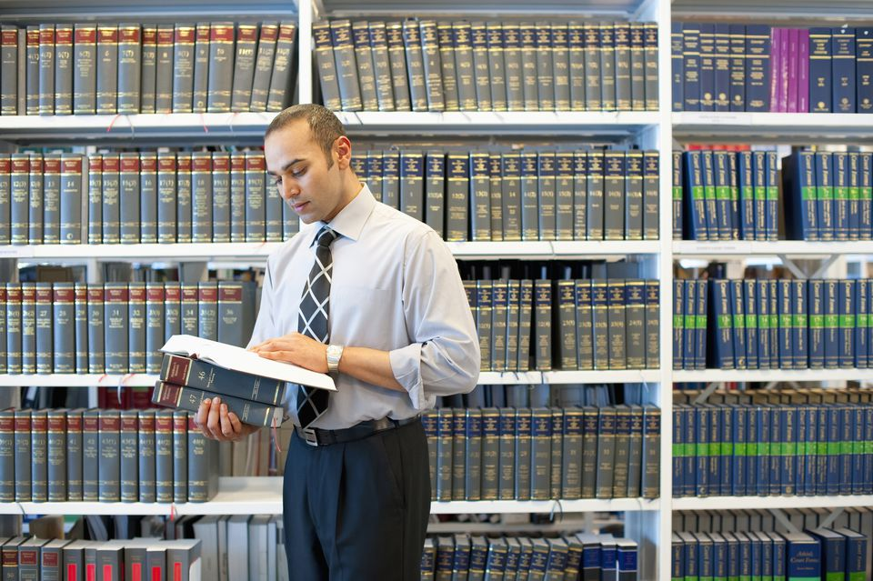 Indian businessman reading book in law library