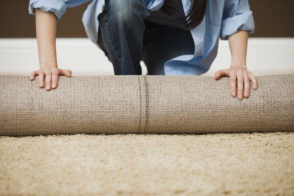 Caucasian woman unrolling carpet