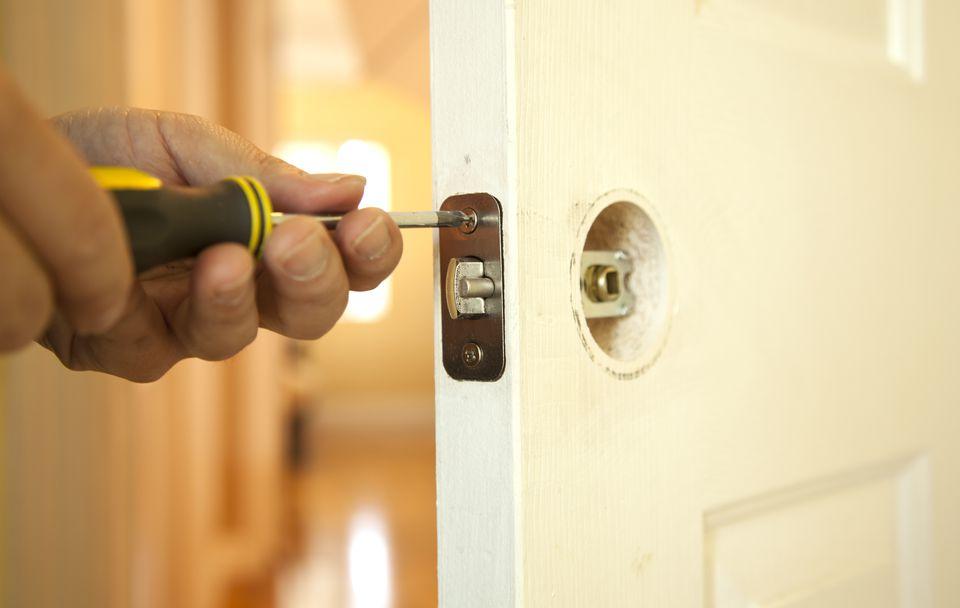 Hands installing a hollow core door's lock
