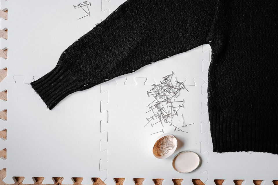 A black sweater with pins on a board