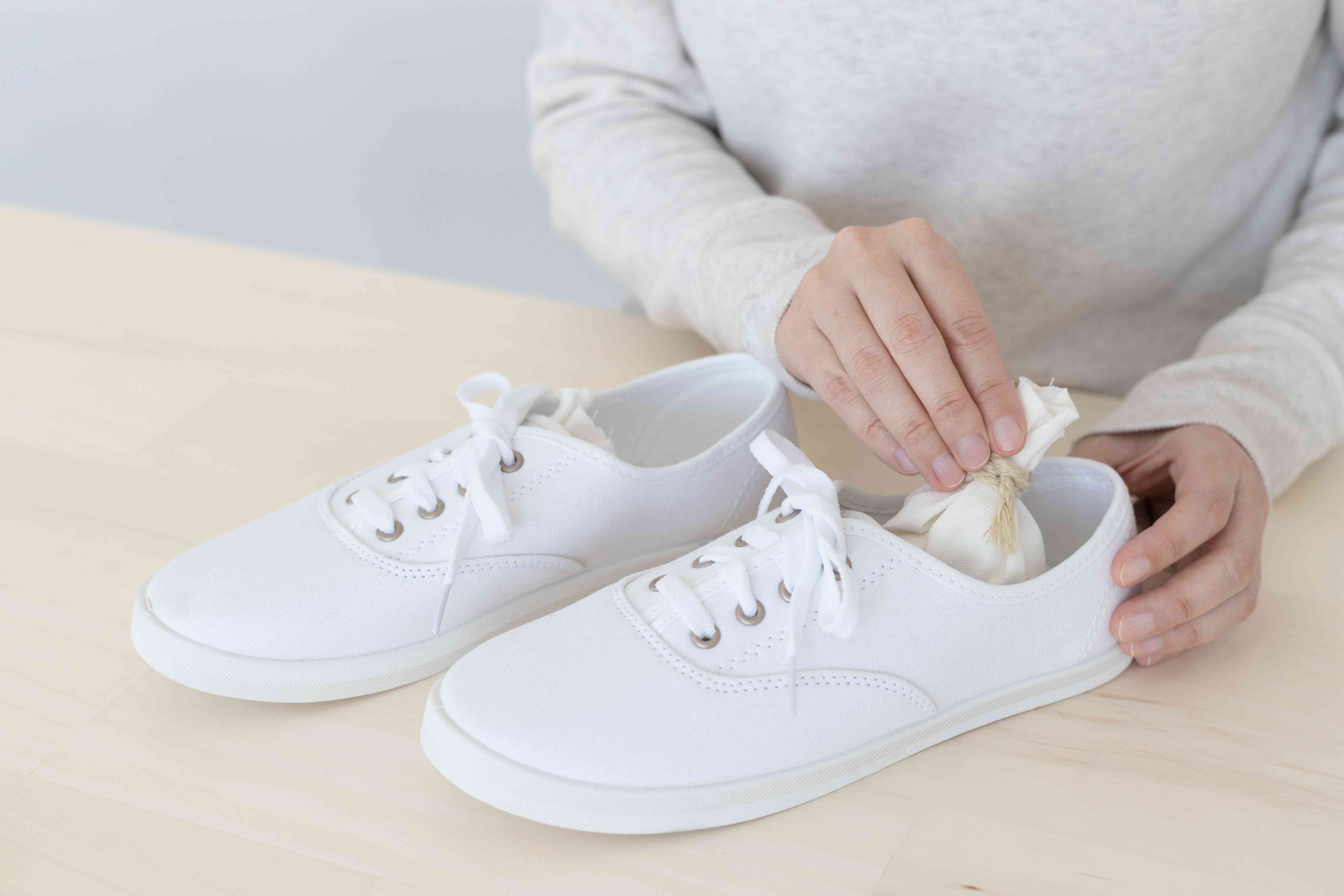 Bag of baking soda placed inside canvas shoes