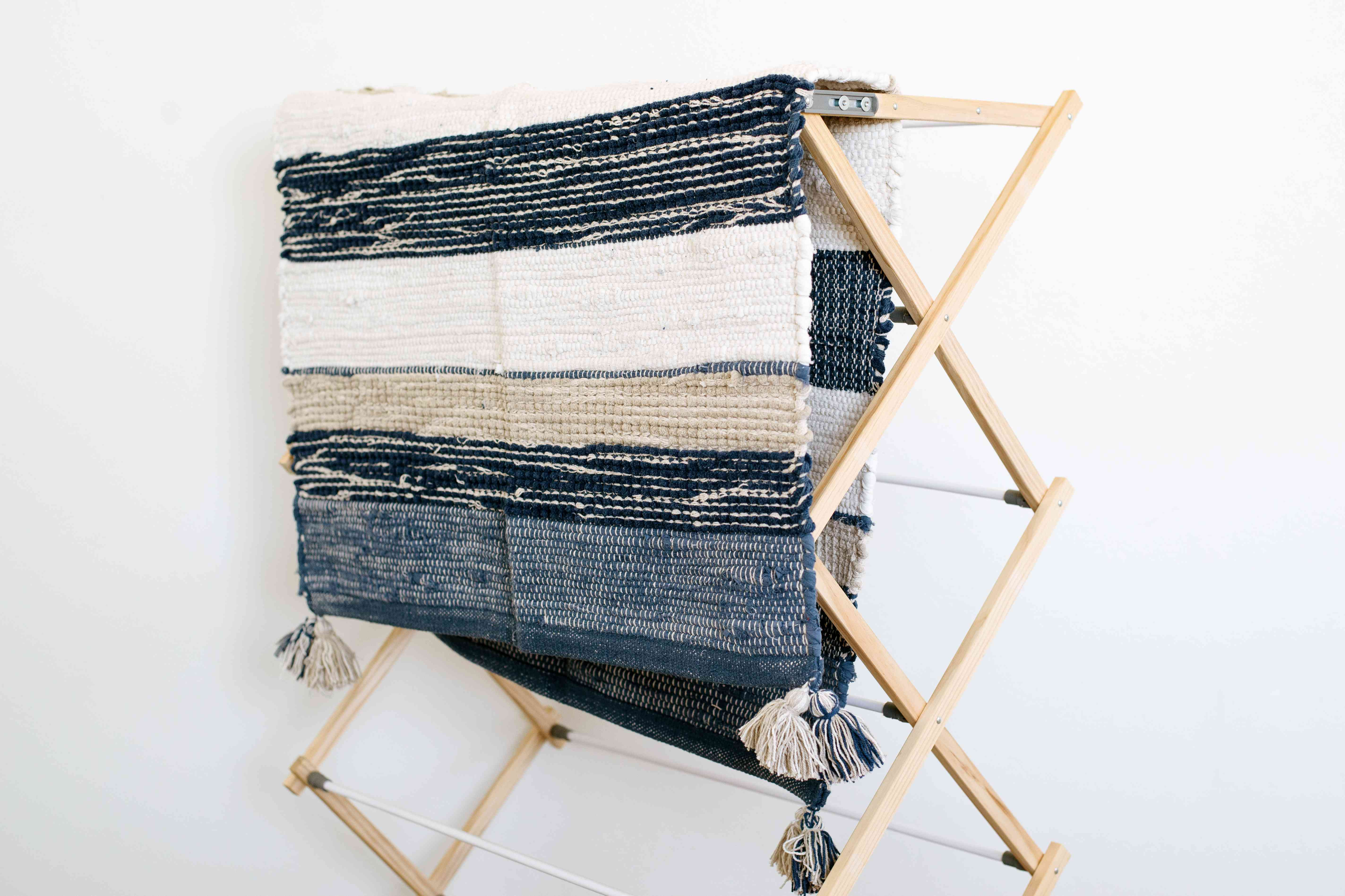Throw rug on wooden drying rack