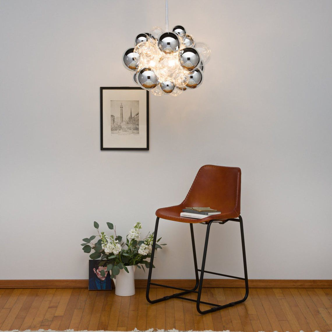 Chrome 31 Bubble Chandelier hangs above a brown chair