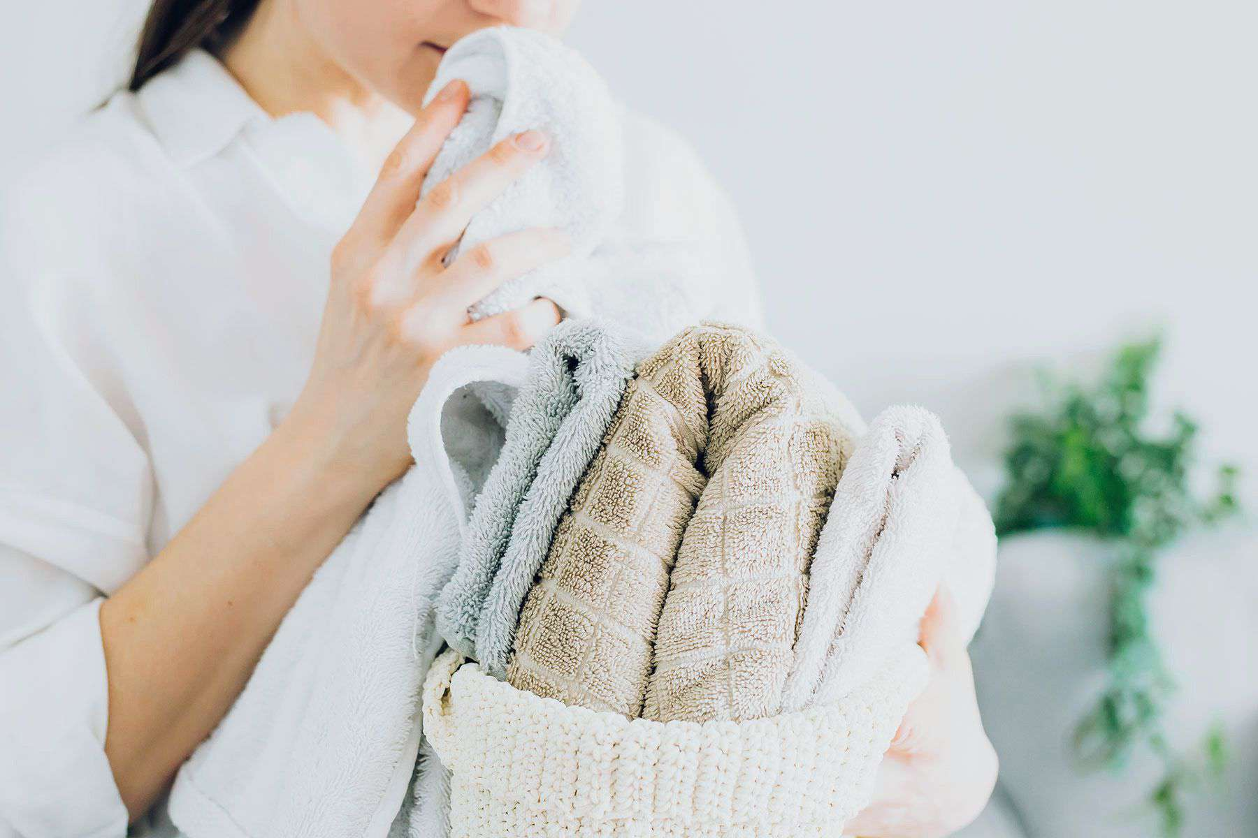 Folded towels in woven holder being smelled