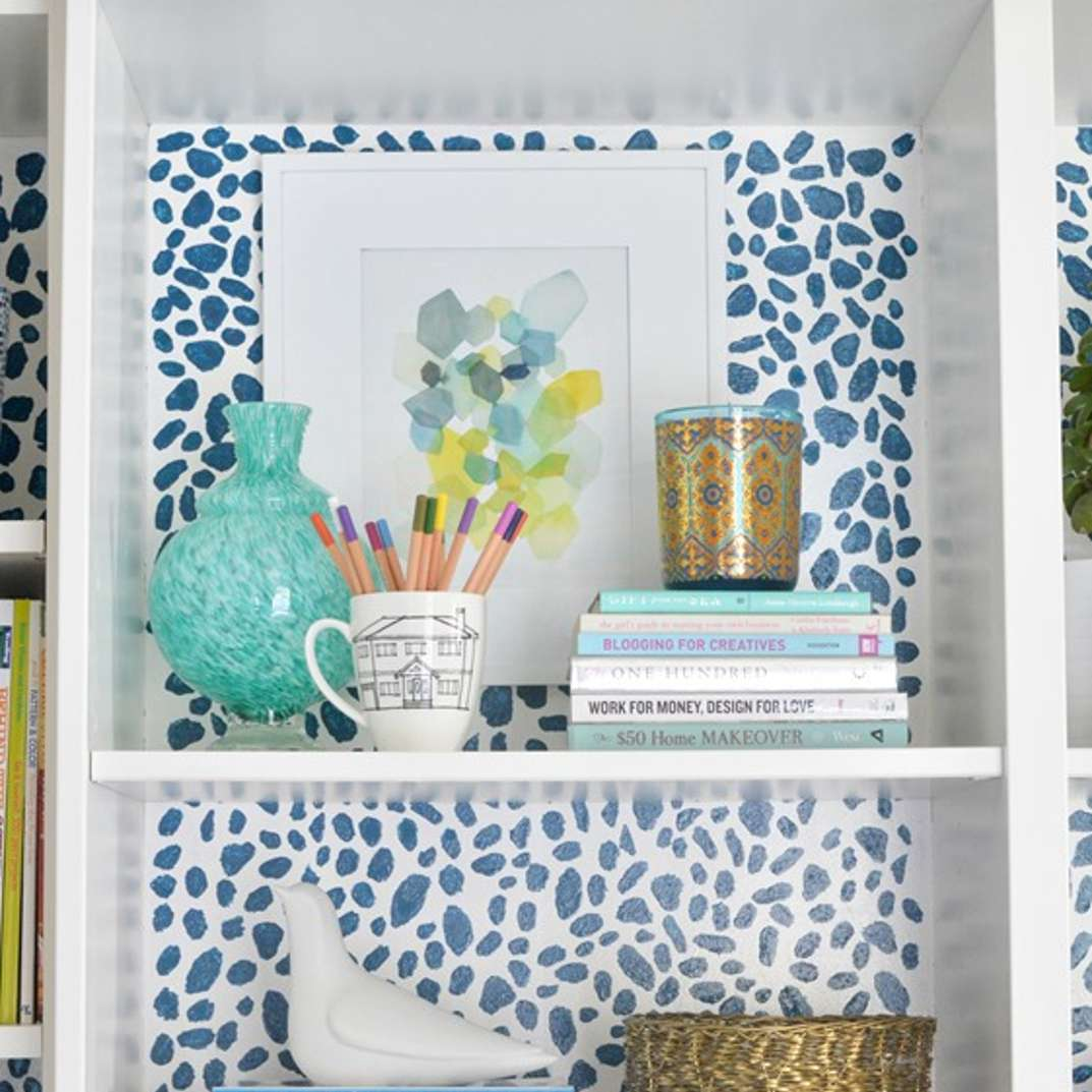 Sponge painted cheetah spots on the back wall of a bookcase.
