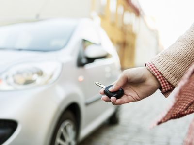 Cropped image of businesswoman using remote control key to unlock car