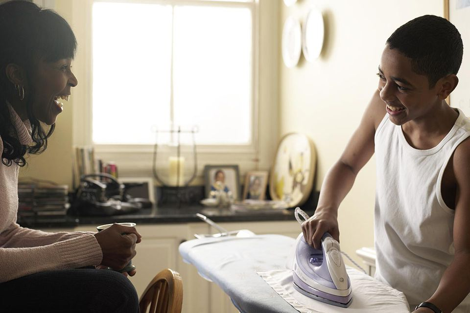 Boy (12-13) ironing shirt smiling to mother in kitchen