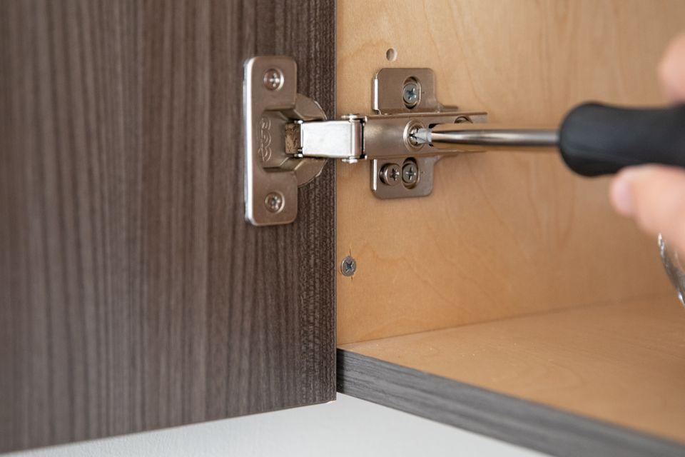 person adjusting a cabinet door