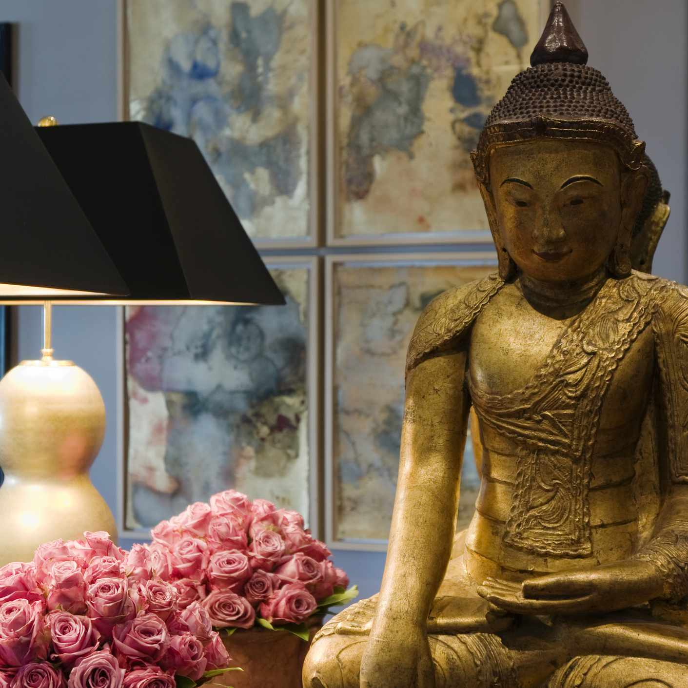 buddha on a table with mirror, flowers, and lamp