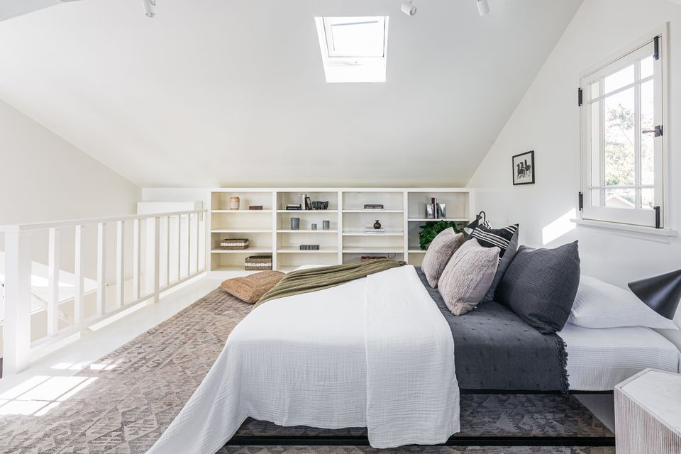Lofted bedroom with white railings and skylight with shelves on the back wall