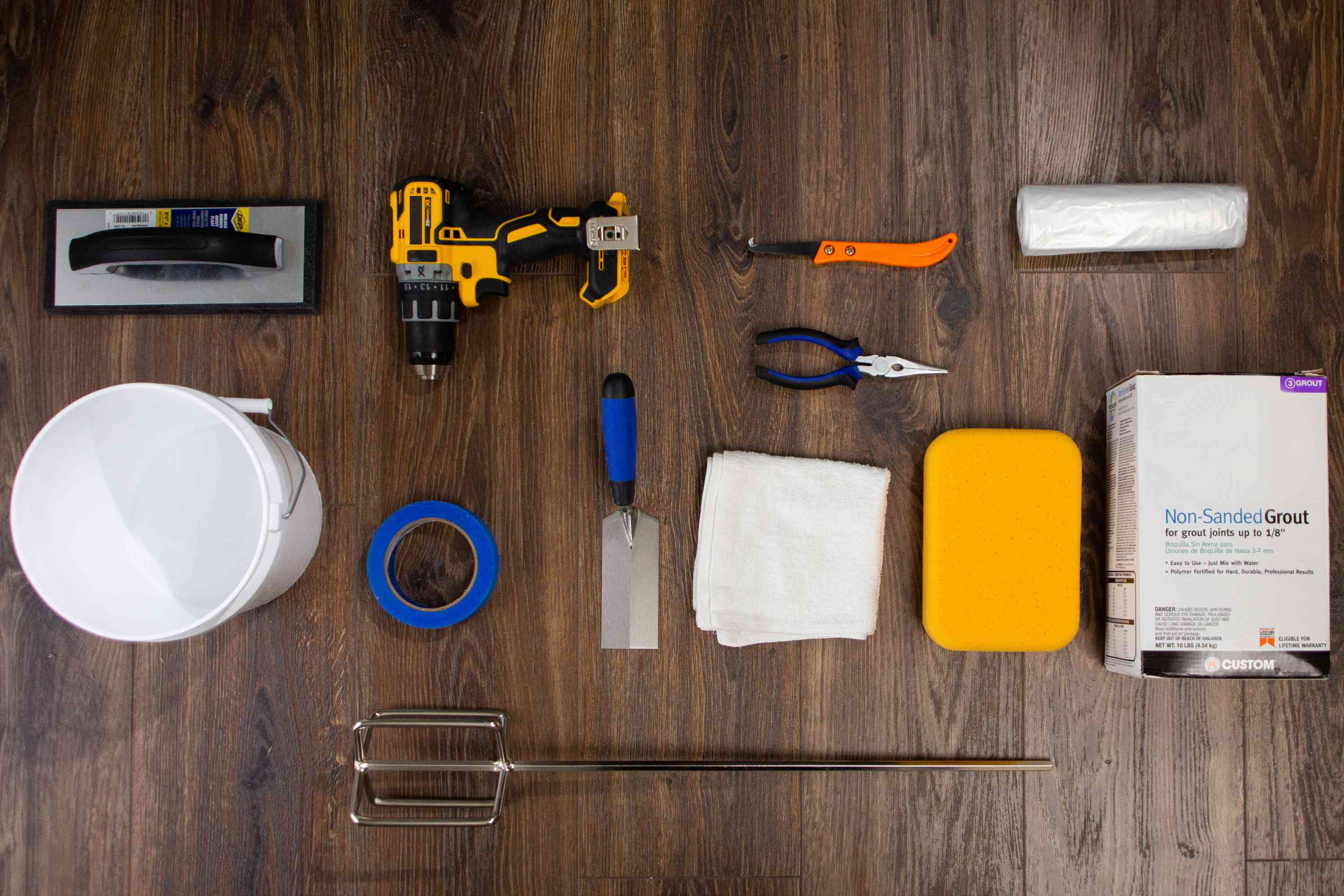 Materials and tools to apply grout to ceramic wall tile on wooden surface