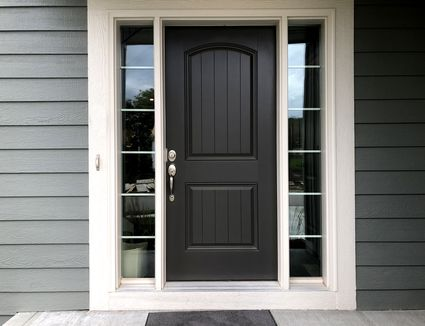 Front door of house, from exterior, black with side paneling of glass.