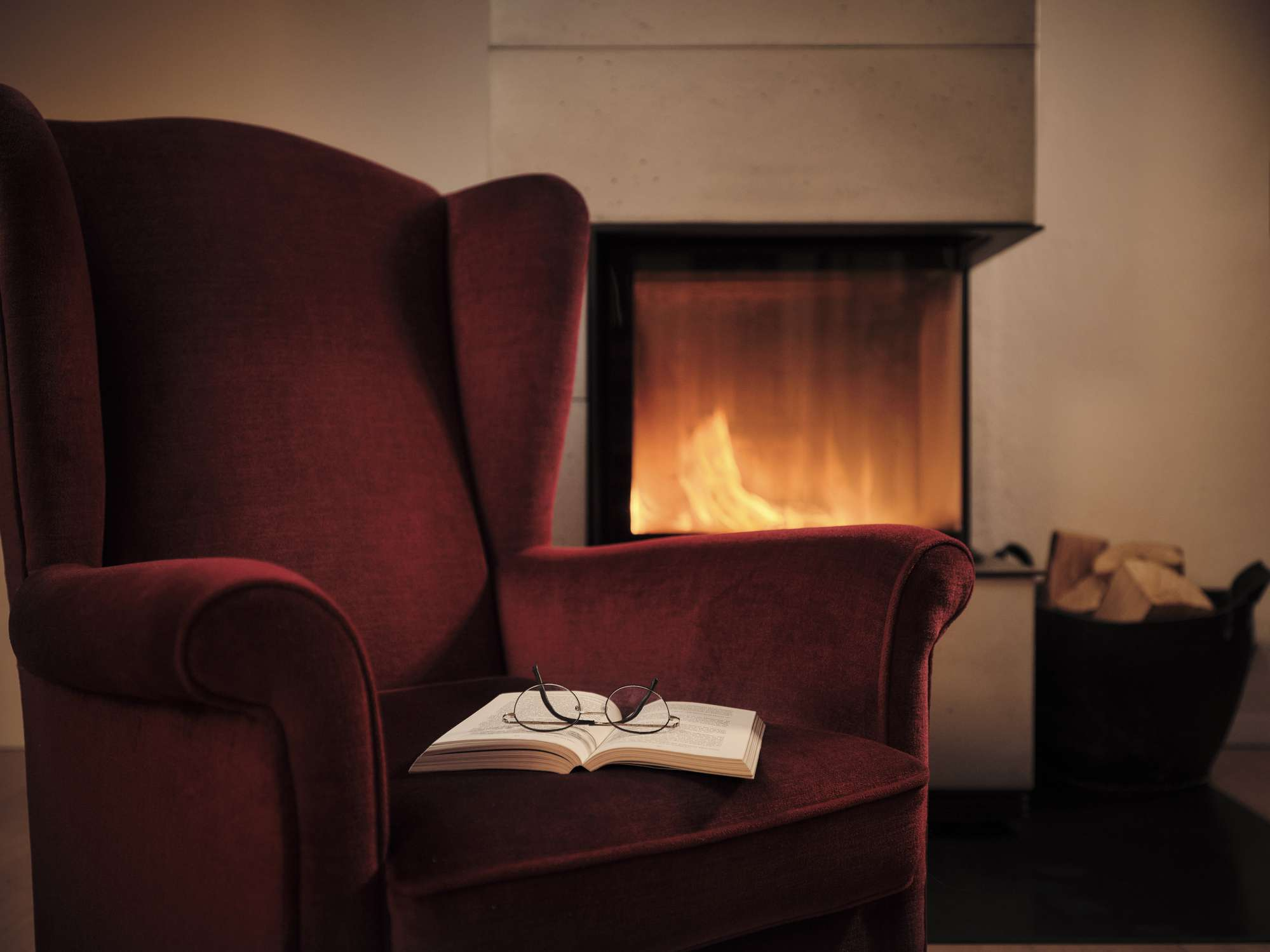 A wingback chair in front of a fireplace
