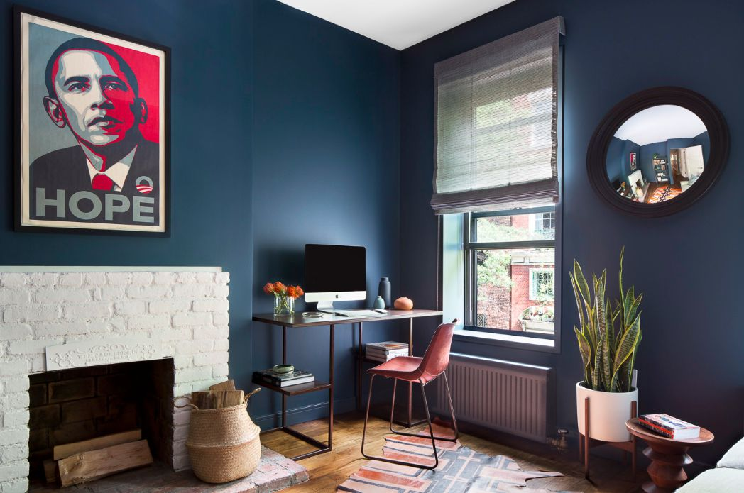 blue bedroom with a white brick fireplace