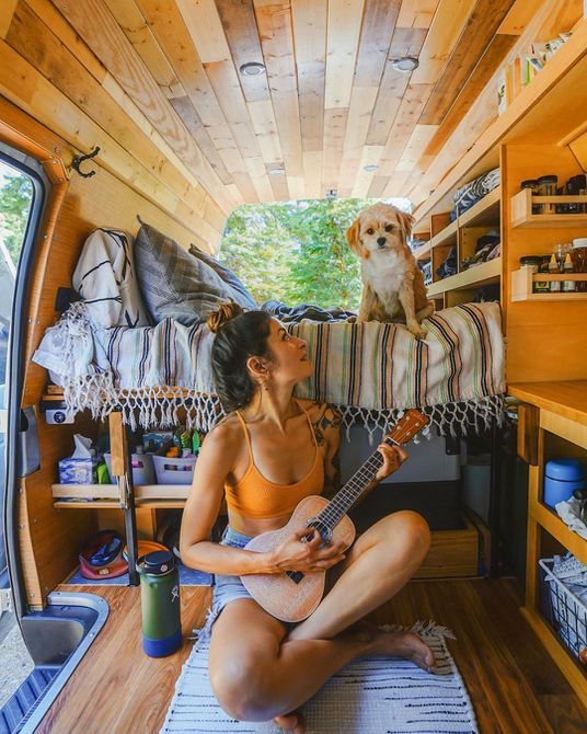 A woman playing a ukulele in a van looking at a dog sitting on the bed above her