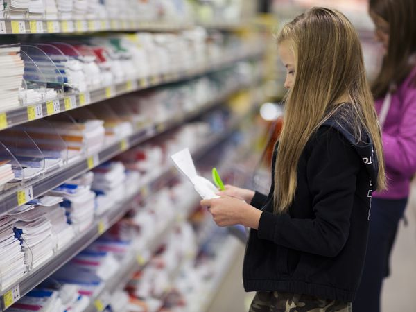 Girl looking at shopping list in school supplies aisle of store