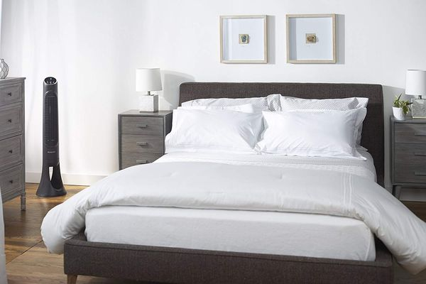 A neutral tone bedroom with a tower fan in the corner