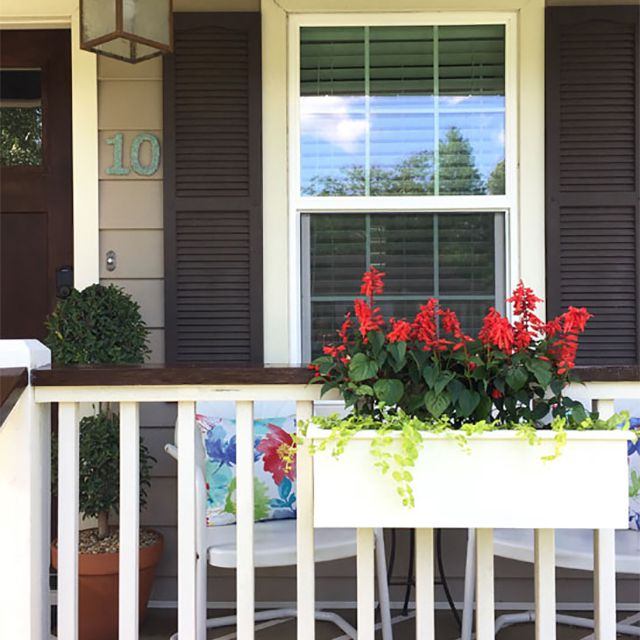 White porch planter with red flowers