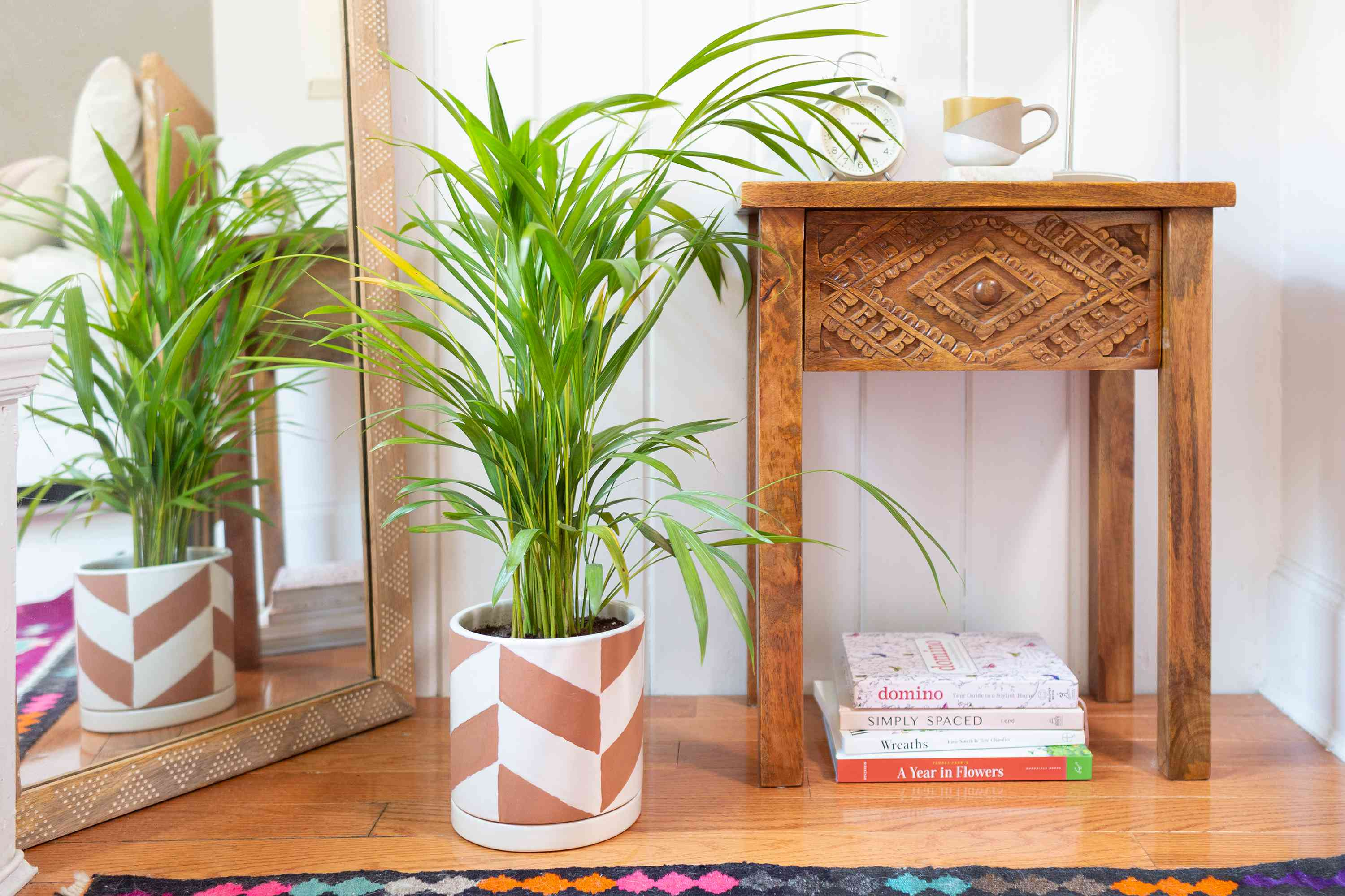 Areca palm in white and brown patterned pot next to mirror and wooden side table