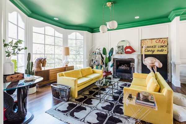 a living room with emerald green ceiling, yellow sofas, a black and white rug, and large windows that flood the room with light