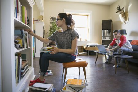 Woman Sorting Through Books In Bookcase