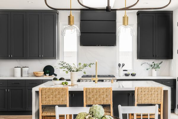 Kitchen with black cabinets and white island with natural woven chairs