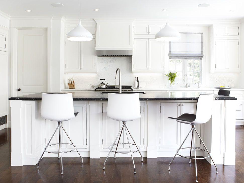 Una cocina con encimeras de mármol negro mate y una placa para salpicaduras de mármol blanco